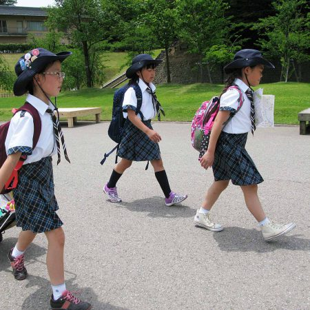 Three school girls in uniforms with a pushcart