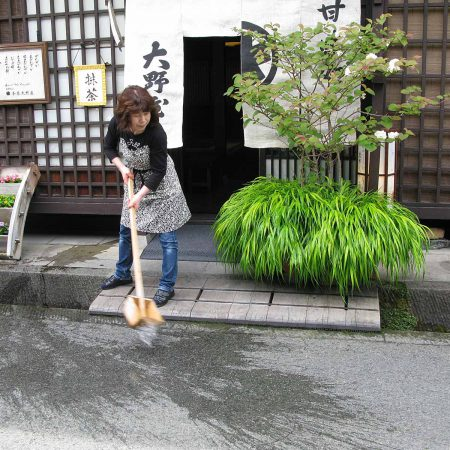 In Takayama a woman washes the entrance floor of a restaurant with water