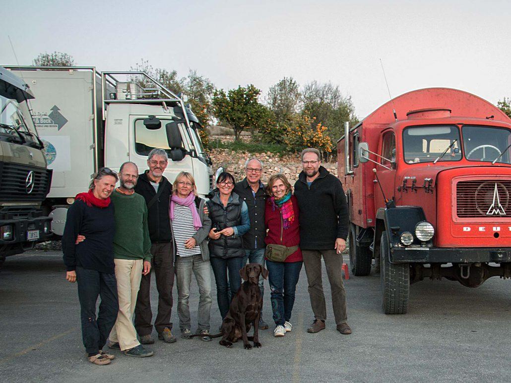 Acht glückliche Menschen am Ziel nach einer spannenden Fahrt mit vier LKWs durch die Berge