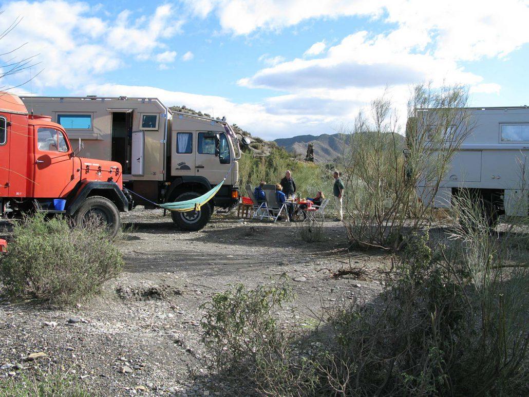 Freies Campen im trockenen Flussbett mit mehreren Fahrzeugen