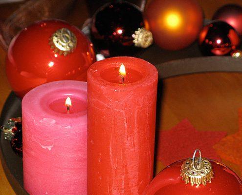 Weihnachtsdekoration mit roten Kerzen und Kugeln