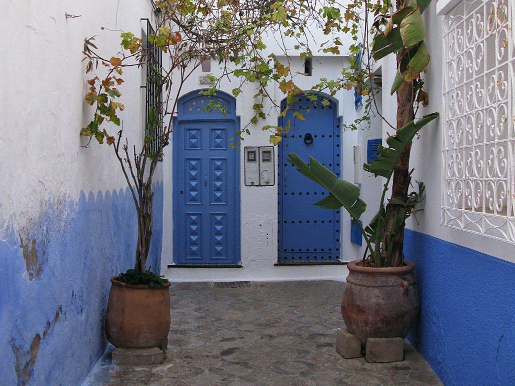 Eingangsbereich mit zwei blau gestrichenen Haustüren in Asilah