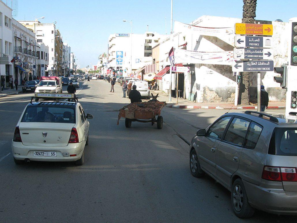 Alltagssituation im Straßenverkehr mit Autos, Fußgängern und Eselkarren