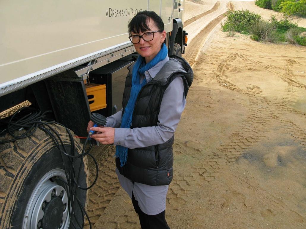 Petra lässt Luft aus den LKW-Reifen für die Fahrt in den Dünen