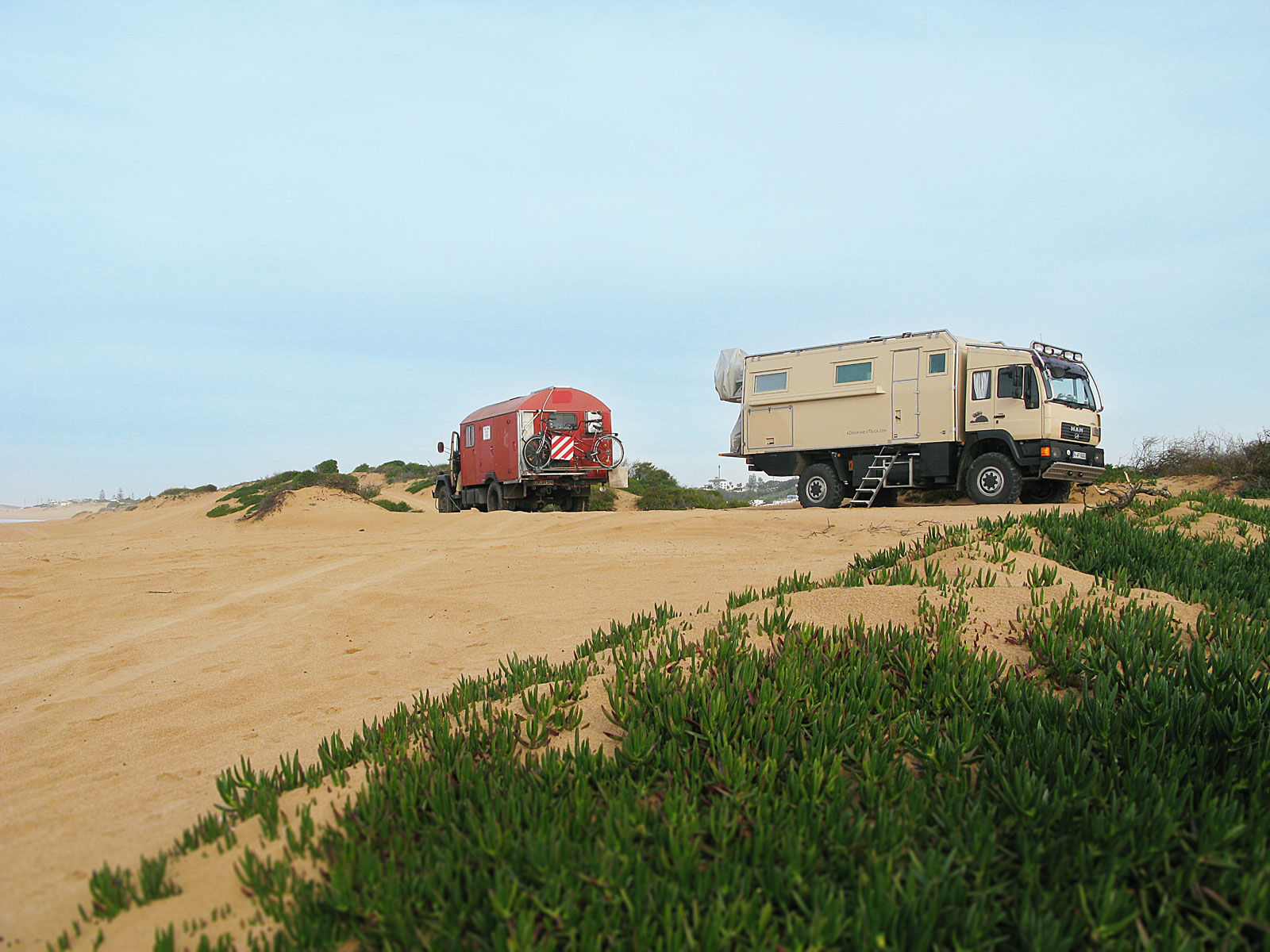 Two mobile homes park in the dunes on a beach in Morocco