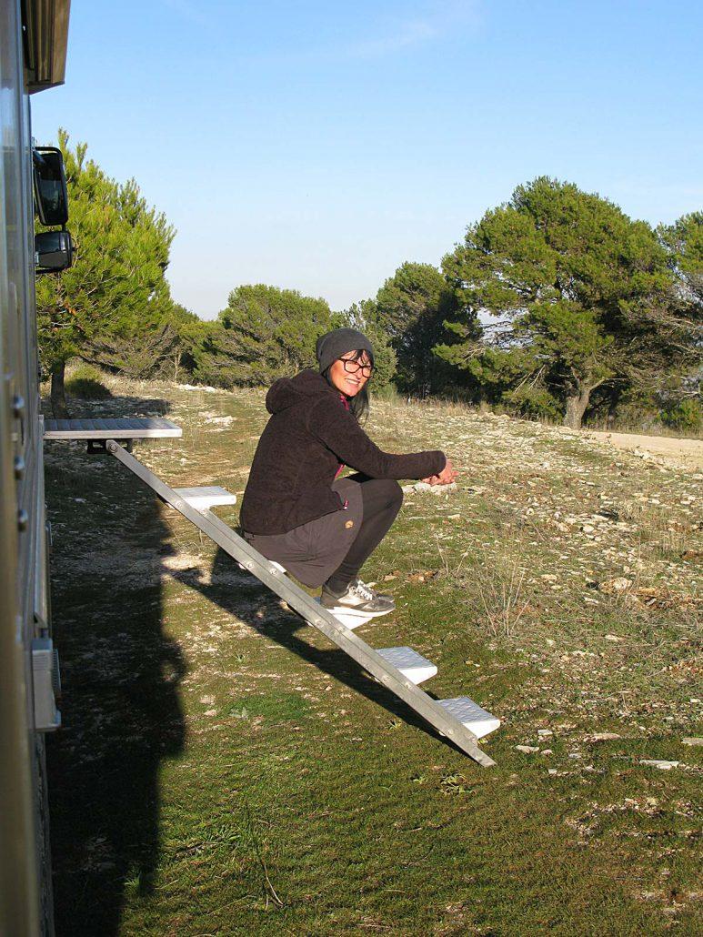Petra sitzt auf den Stufen ihres Campers