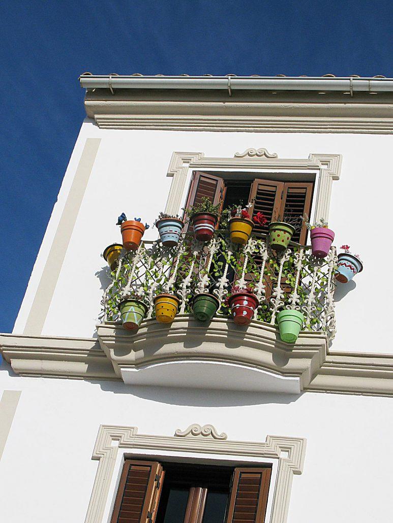 Fenster in Olvera mit bunten Blumentöpfen