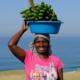 Elize trägt eine blaue Plastikschüssel mit Bananen auf dem Kopf