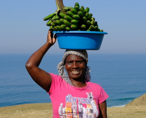 Elize is carrying a blue bowl with bananas on her head