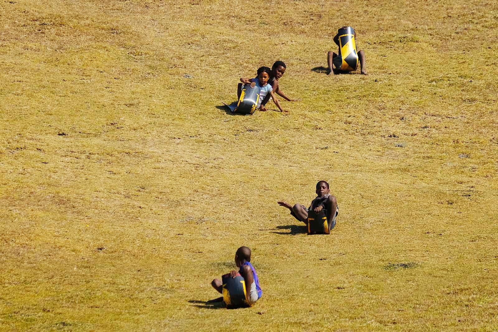 Kinder an der Coffee Bay rutschen auf Schildern den Grashang hinunter